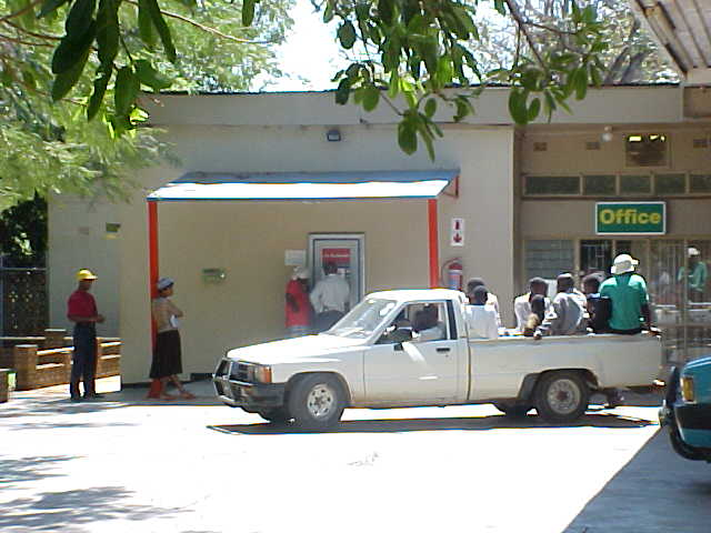 An employer of the gas station helps out the people at the money-robot, as most of the people save and collect their money from their own bank account.