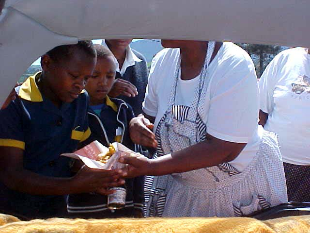 Unfortunately this did not make Shumis business any good. She only made a little 30 Rand today. Here you see here sell the chicken feet, wrapped in a piece of newspaper, to the kids at the school.