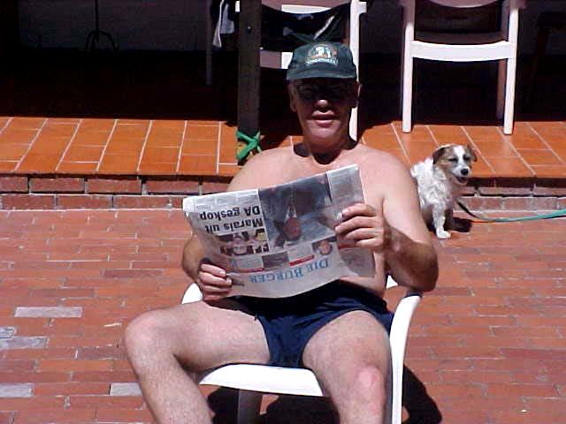 As her father is enjoying the newspaper and the sun in the back garden.