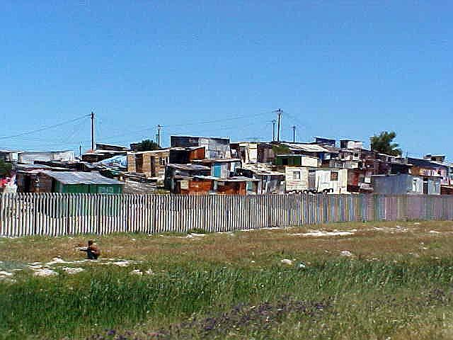 Views of squatted camps along the road, built on the Cape Town flatlands, an area that is known to fill up with water from the mountains in the wintertimes. Most sheds are built as high as possible. Do you see the electricity wires?