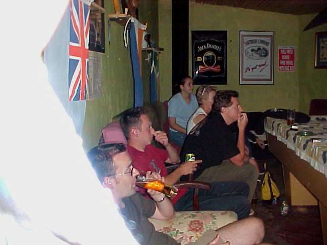 At the pub, seperate from the hostel, all the guests were watching an important rugby game on television.