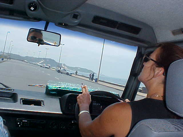 Linda in her car during a tour around town, with the ocean in the background.