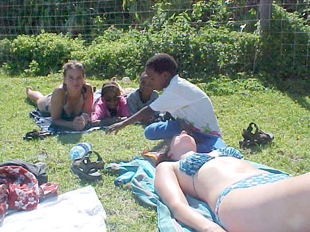 Sunbathing in the grass near the beach, joined by three young kids.