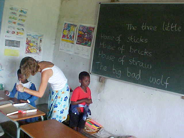 She is teaching the young kids to write and read and mathematics.