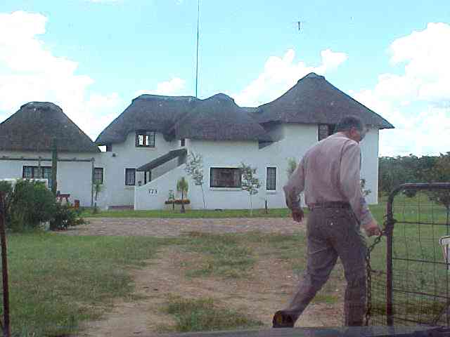 Luis opens the gate to his plot in Centurion. At the background the handbuilt house of the Lopes family.