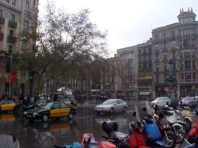 Walking through the rain in Barcelona, full with funny little scooters and black and yellow taxis.