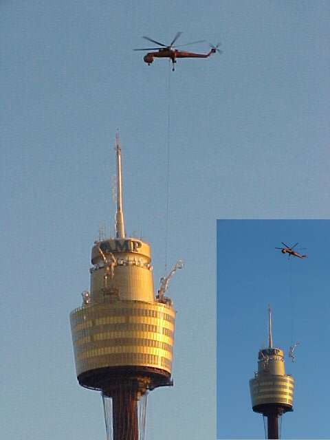 A cargo helicopter removes the Olympic statues off the AMP-tower.