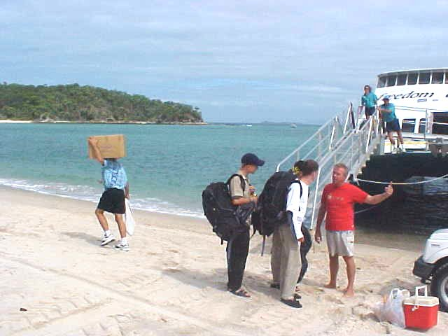 At arrival on the beach of GKIsland, Geoff, the manager of the Holiday Village, talks to some backpackers who haven<#k#>'t arranged any accommodation yet. Geoff suggest them to take a look at his place and they join along.