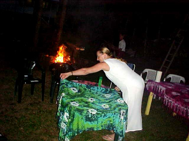 While the fire is lit, Anne prepares the dining tables for the barbecue party of tonight.