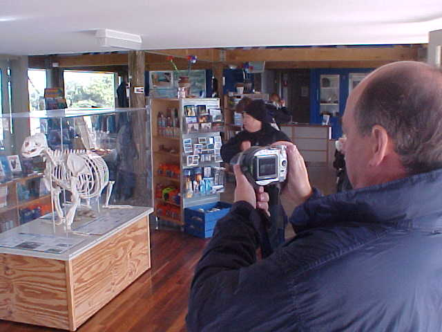 At the Sealbay tourism shop Marc takes photos of the exhibitions with his digital camera.