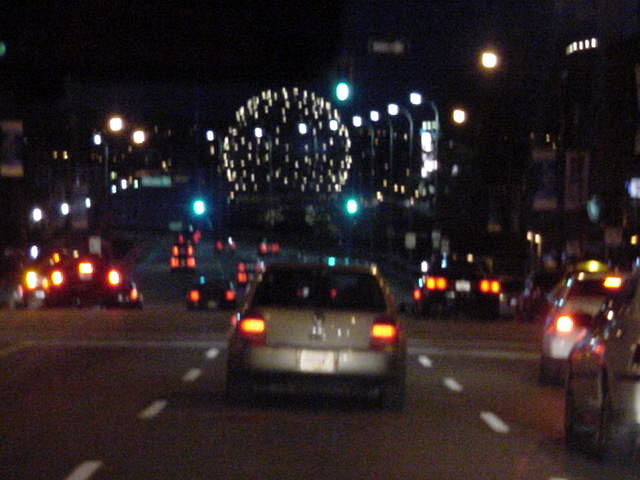 On the way to the ice factory the ball of Science World lights up above the road.