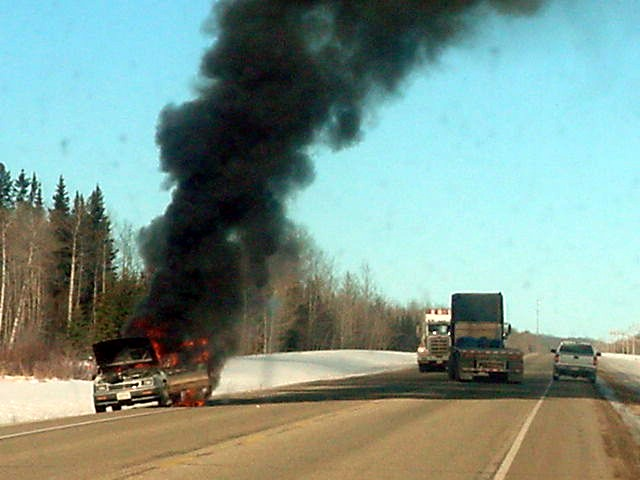 On the road from Grimshaw to Manning I got to see something exciting finally. A woman got off the road to see where the smoke was coming from. When she opened the front, she saw the flames, got her kids out of the car and run away. Big trucks block the road as this was a dangerous situation if you pass by. This photo was taken before the fuel tank exploded.