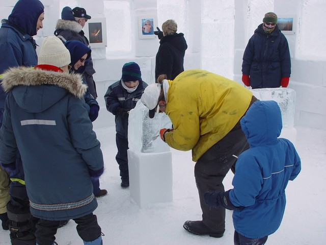The Snowking teaching kids how to carve the ice.
