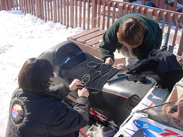 Outside Eva and her sister are sewing the seat of their sons skidoo.