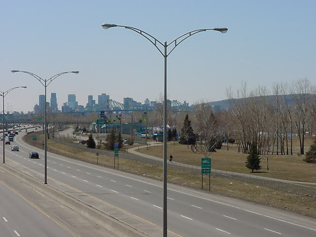 The metropolis of Montreal and the Mont Royal at the right as seen from the walk bridge over the highway.