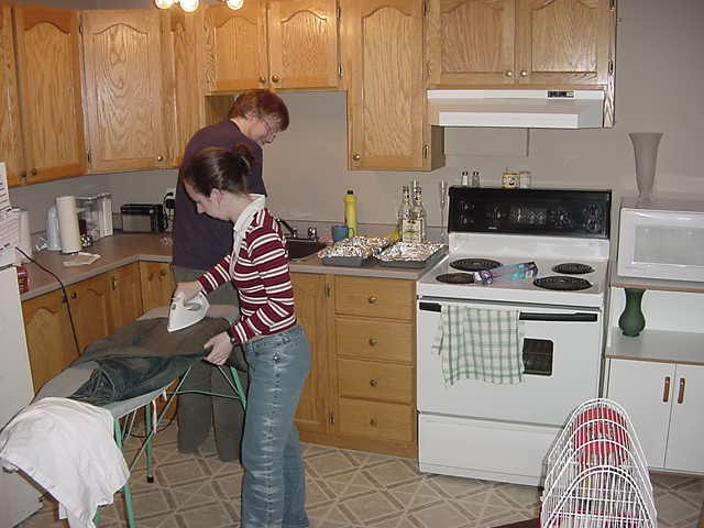 Karl prepares chicken wings and fries for tonight as Sherry does some ironing in the kitchen.