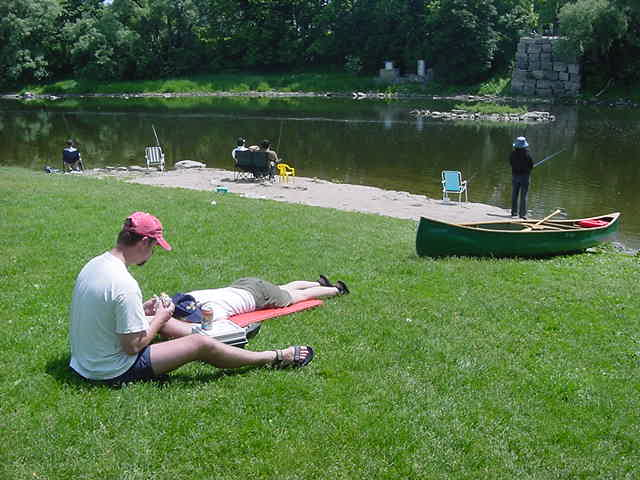 Laura is tired of sitting in the middle of the men in the canoe...