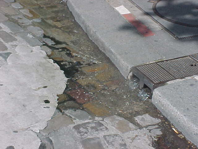 This is how in Paris the streets are cleaned. Just pump up water up the hill and let it flow down the street into a hole... Genious
