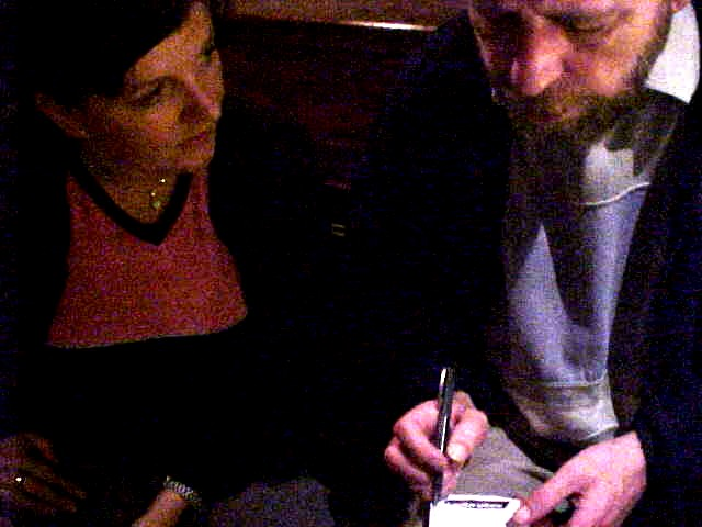 Tonje talks to the journalist Harry, who writes his notes on the insite of his cigarette box top...