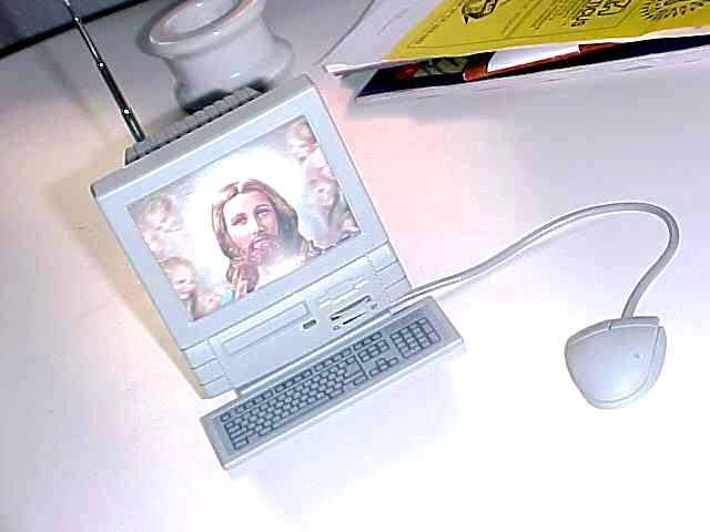 As The Gift from Søren Pors, Lars received this: it is a miniature personal computer with a built-in radio. The attached mouse even lets you scan for a frequenty or even reset it all. The 3D Christ is put into it by Søren as a symbol of the religionation of television...