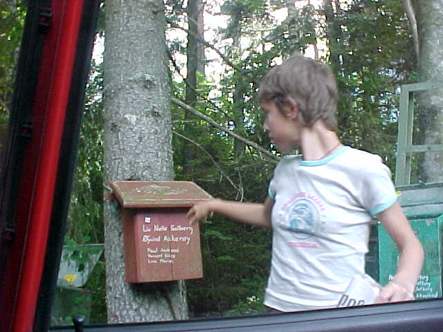 Elaine checks the mail at their mailbox in the beginning of the forrest to their house...
